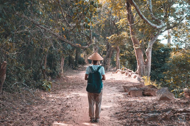 One tourist visiting Angkor ruins amid jungle, travel destination Cambodia. Woman with traditional hat, rear view royalty free stock photography