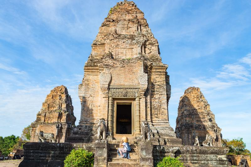One tourist visiting Angkor ruins amid jungle, Angkor Wat temple complex, travel destination Cambodia. Woman with traditional hat royalty free stock image