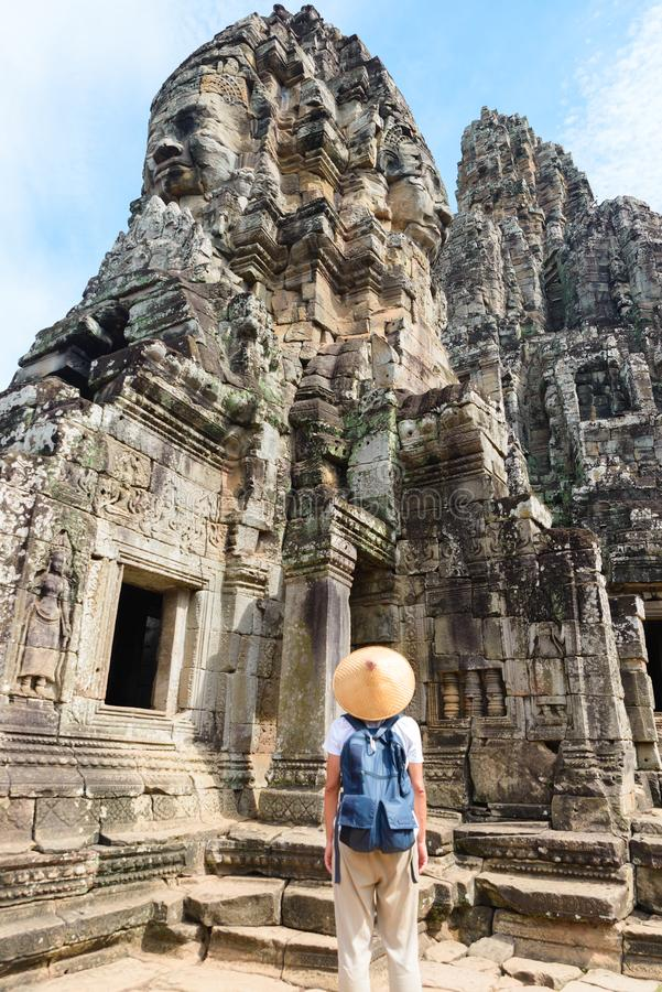 One tourist visiting Angkor ruins amid jungle, Angkor Wat temple complex, travel destination Cambodia. Woman with traditional hat stock photography