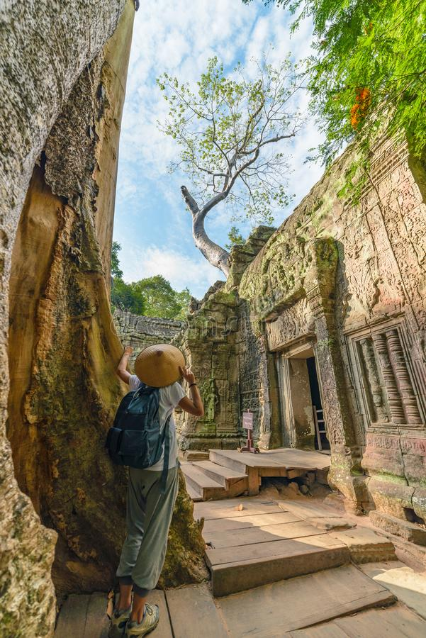 One tourist visiting Angkor ruins amid jungle, Angkor Wat temple complex, travel destination Cambodia. Woman with traditional hat royalty free stock photos