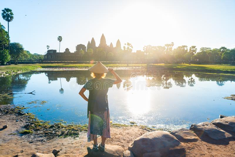 One tourist visiting Angkor Wat ruins at sunrise, travel destination Cambodia. Reflection on water pond and sunburst, woman with royalty free stock photo