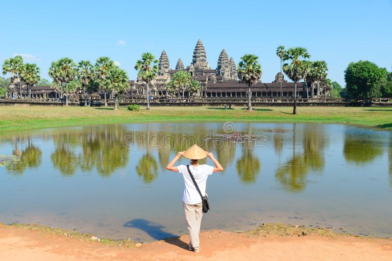 One tourist visiting Angkor Wat ruins at sunrise, travel destination Cambodia. Woman with traditional hat and raised arms, rear stock photos