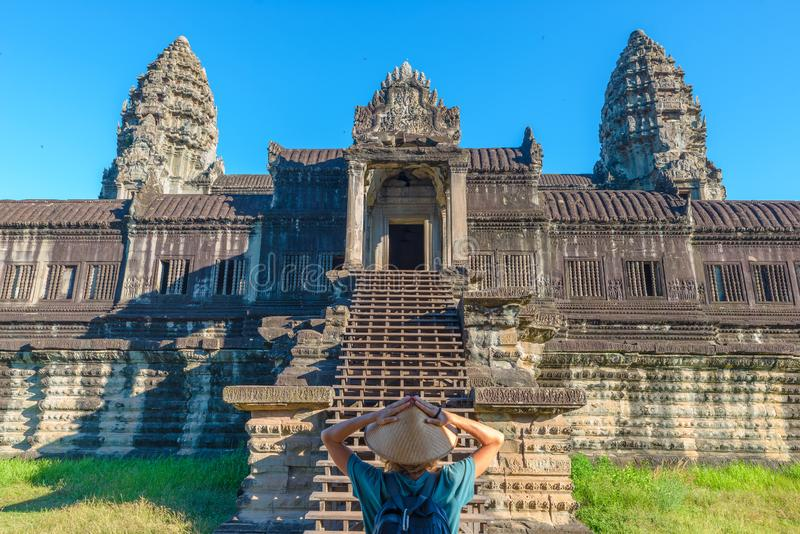 One tourist visiting Angkor Wat ruins at sunrise, travel destination Cambodia. Woman with traditional hat and raised arms, rear royalty free stock photos