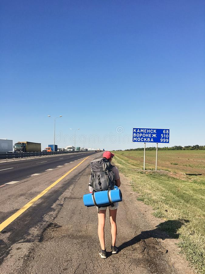 One traveler girl with a backpack walks along the road on a summer sunny day. Back view stock photos