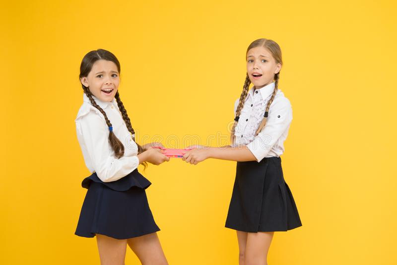 One for two. childrens literature. outraged classmates with workbook. little girls in school uniform. girls can`t share. A book. kids learning grammar. back to royalty free stock photo