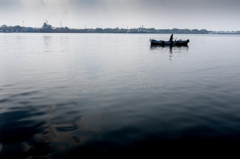 One unrecognisable fisherman on his boat, Kochi, Kerala, India. One unrecognisable fisherman on his boat seen from far away, with no other people, near the royalty free stock photos
