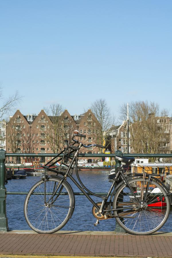 One usual black bike near the canal in the center of Amsterdam in the autumn day. One usual black bike near the canal in the center of Amsterdam in the sunny royalty free stock photos