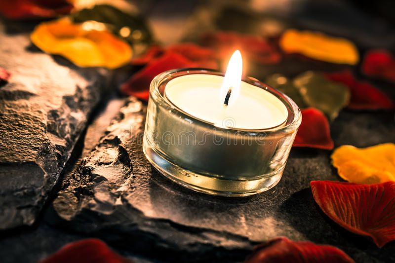 One Valentine Candle Light On Slate With Rose Petals And Leafs stock photos