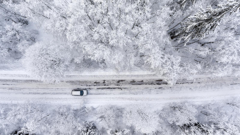 One vehicle driving through the winter snowy forest on country road. Top view royalty free stock photo