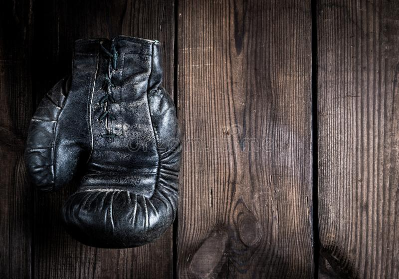 One very old leather black boxing glove with laces royalty free stock photo