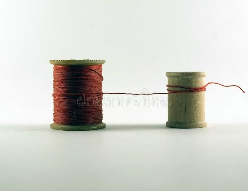 One Vintage Wooden Thread Spool With Red Thread Connected to an Empty Smaller Vintage Wooden Thread Spool royalty free stock image