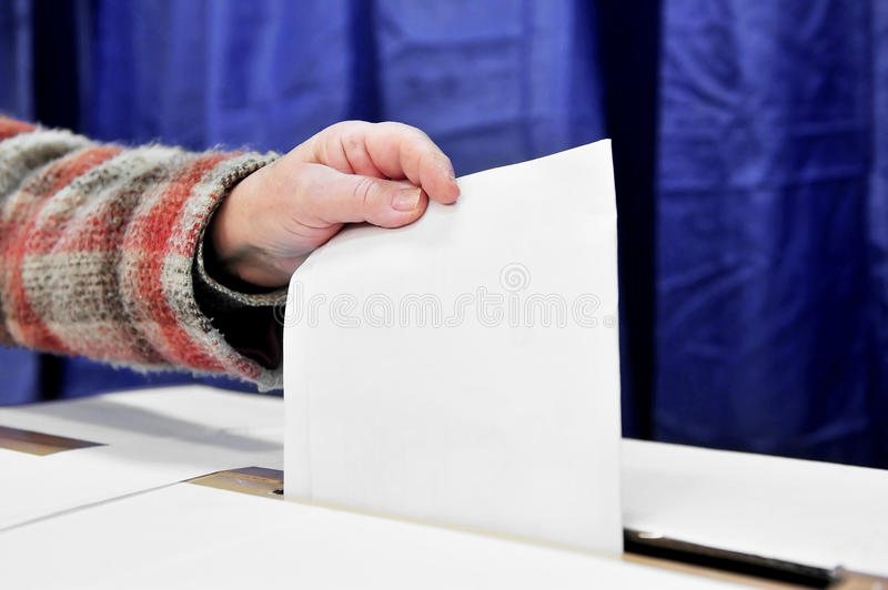 One vote. Close-up of a person hand putting a vote in the ballot box royalty free stock photography