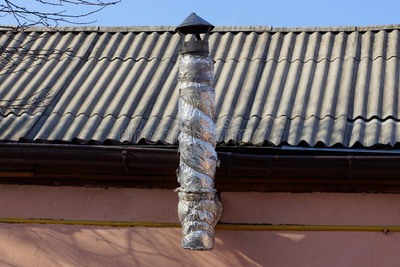 One warmed long metal pipe on a gray slate roof against a blue sky stock photos