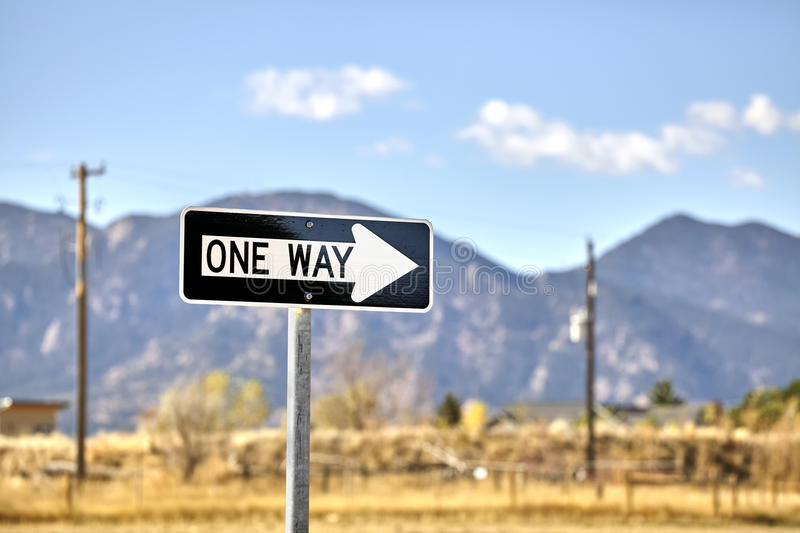 One way road sign with blurred mountains background.  royalty free stock photography