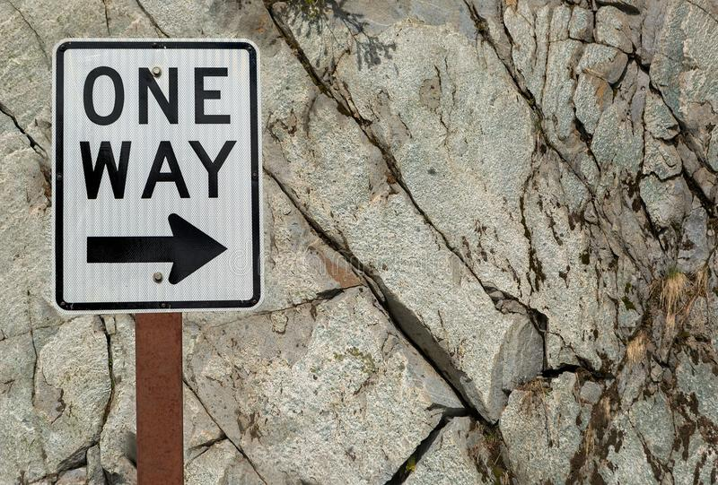 One Way Sign Against Rock Wall Background. One Way highway directional road sign against grunge texture rock wall royalty free stock image
