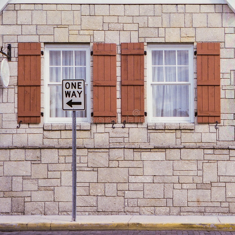 One Way Sign In Front of Windows royalty free stock image
