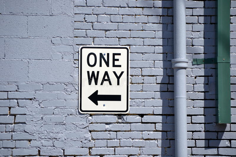 One Way Sign on Brick Wall stock photography