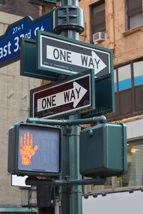 One way street sign pole in New York with red traffic light stock photography