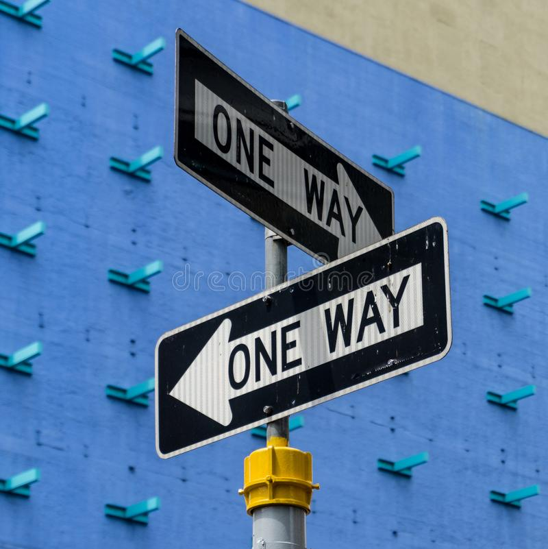 One Way street signs. Posing oneway street signs in the Streets of Manhattan on blue background. view from below stock photos