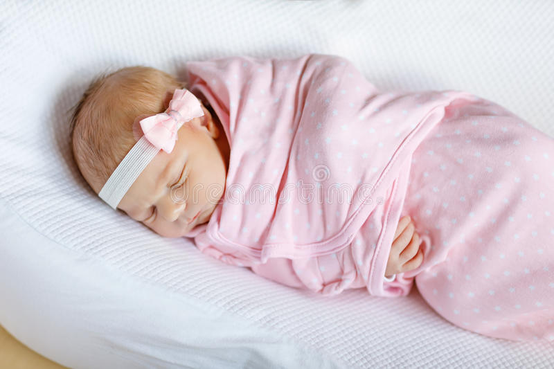 One week old newborn baby girl sleeping wrapped in blanket royalty free stock photo