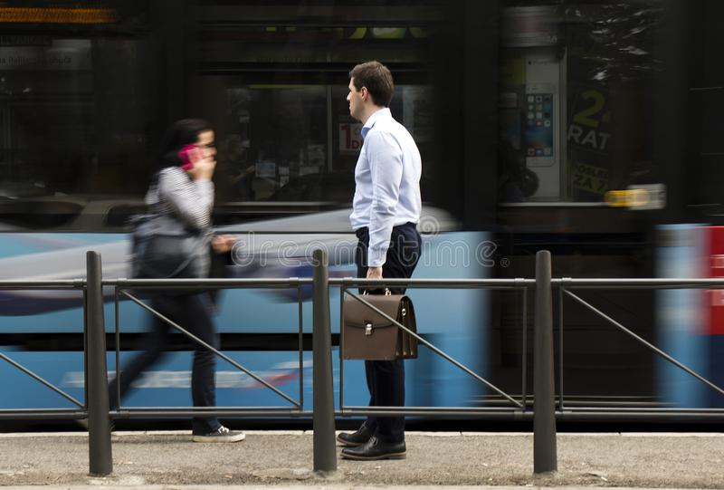 One white-collar man with briefcase waiting at bus stop. Belgrade, Serbia - April 24, 2018 : One white-collar man with briefcase standing at a bus stop and royalty free stock photography