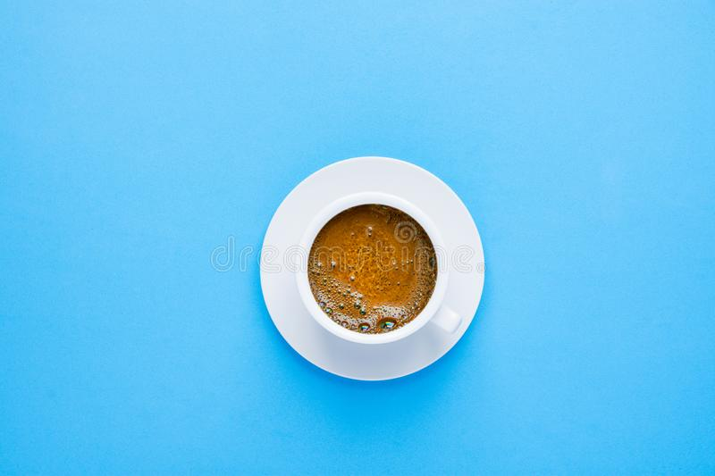 One white cup of freshly brewed black coffee with tan-colored crema foam on saucer on light blue background. Top view. Morning breakfast energy caffeine royalty free stock image