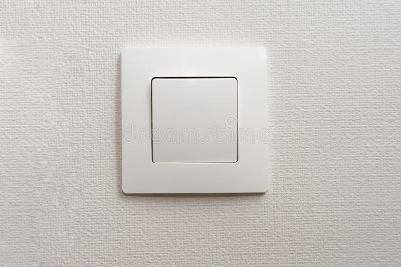 One white light switch, turn on or turn off the lights hanging on the white wall in the room.  stock photography