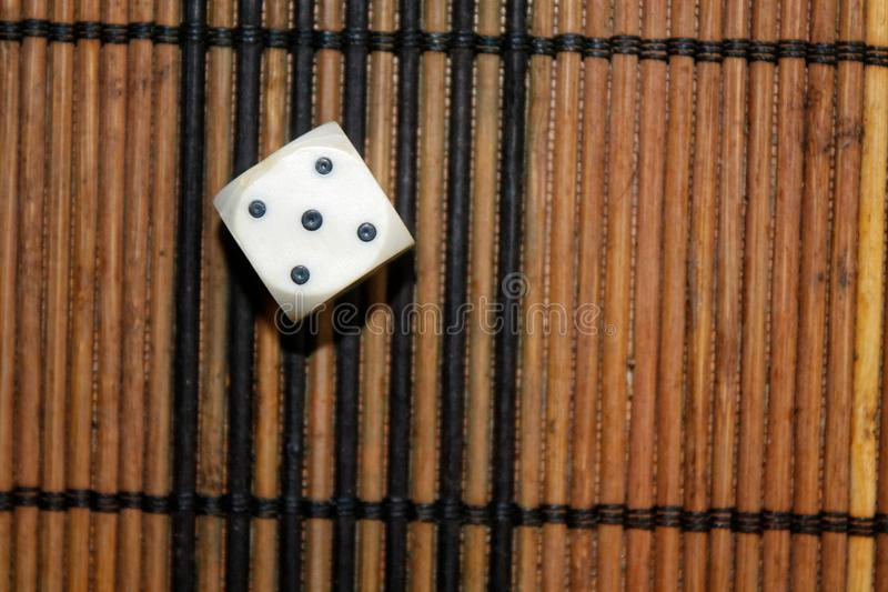 One white plastic dice on brown wooden board background. Six sides cube with black dots. Number 5 royalty free stock photography
