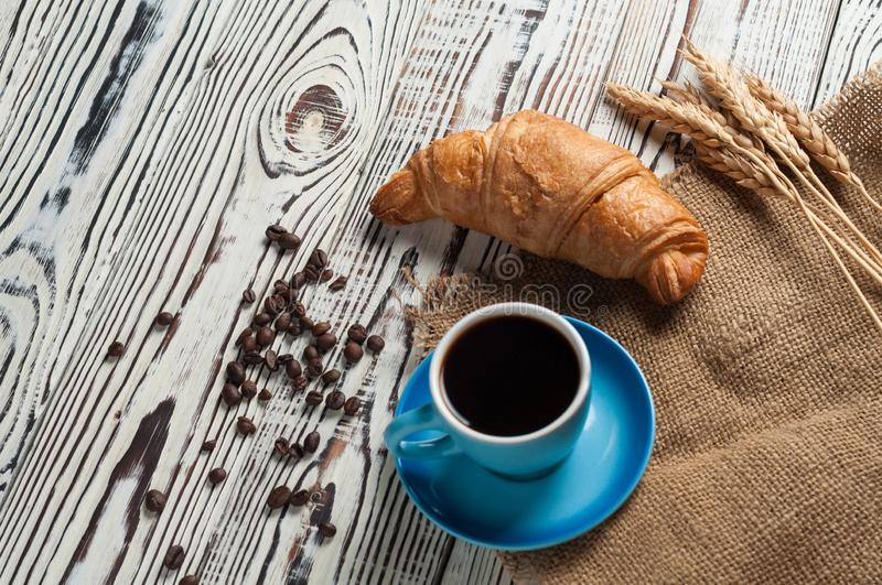 One whole baked croissant near bunch of wheat, full blue ceramic cup of fresh black coffee. On sackcloth and old white rustic wooden table royalty free stock photos