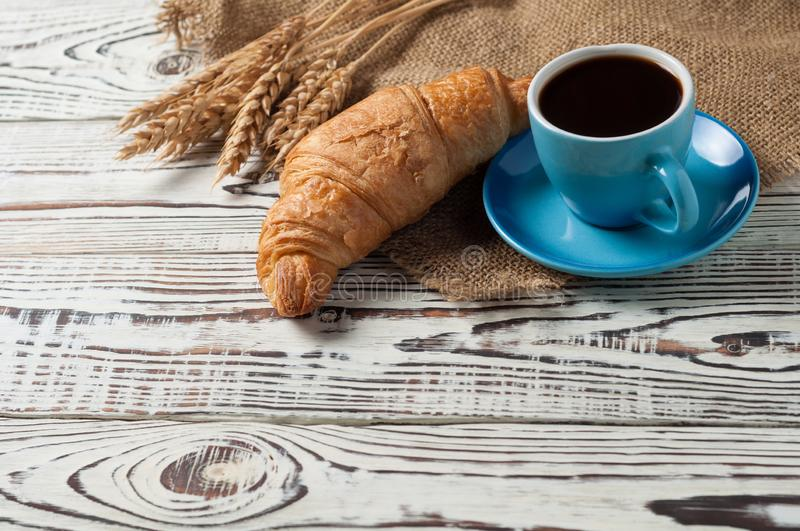 One whole baked croissant near bunch of wheat, full blue ceramic cup of fresh black coffee on sackcloth and white rustic woode. One whole baked croissant near royalty free stock images
