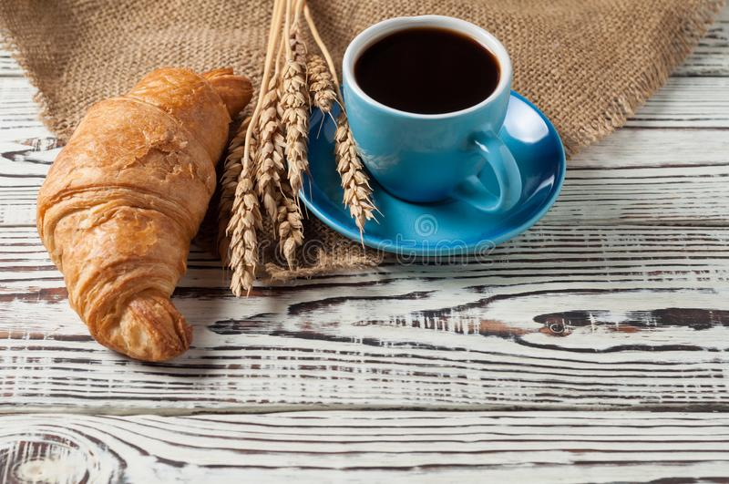 One whole baked croissant near bunch of wheat, full blue ceramic cup of fresh black coffee on sackcloth and white rustic woode. One whole baked croissant near royalty free stock photo