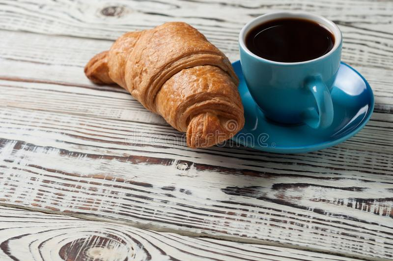 One whole baked croissant near full blue ceramic cup of fresh black coffee on white rustic wooden table. One whole baked croissant near full blue ceramic cup of royalty free stock photo