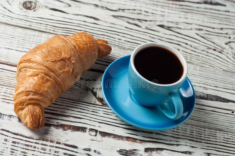 One whole baked croissant near full blue ceramic cup of fresh black coffee. On old white rustic wooden table stock photos