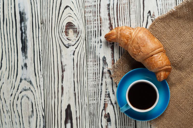 One whole baked croissant near full blue ceramic cup of fresh black coffee on sackcloth and white rustic wooden table. One whole baked croissant near full blue royalty free stock photos