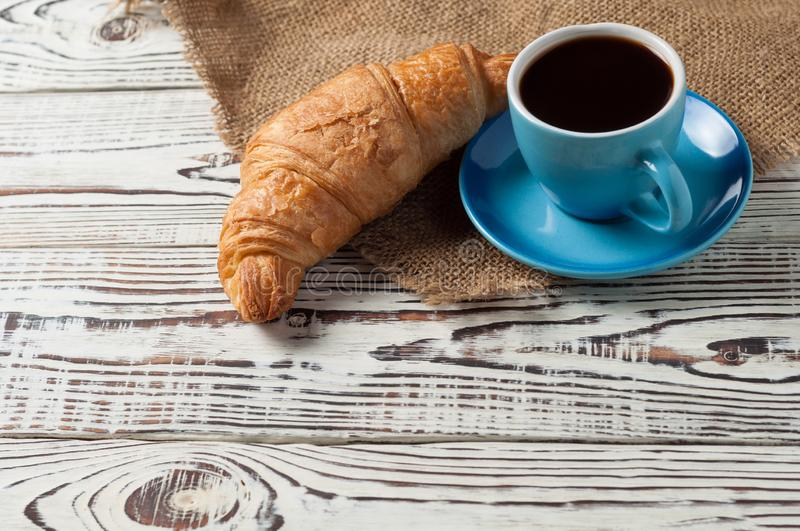 One whole baked croissant near full blue ceramic cup of fresh black coffee on sackcloth and old white wooden table. One whole baked croissant near full blue royalty free stock photo
