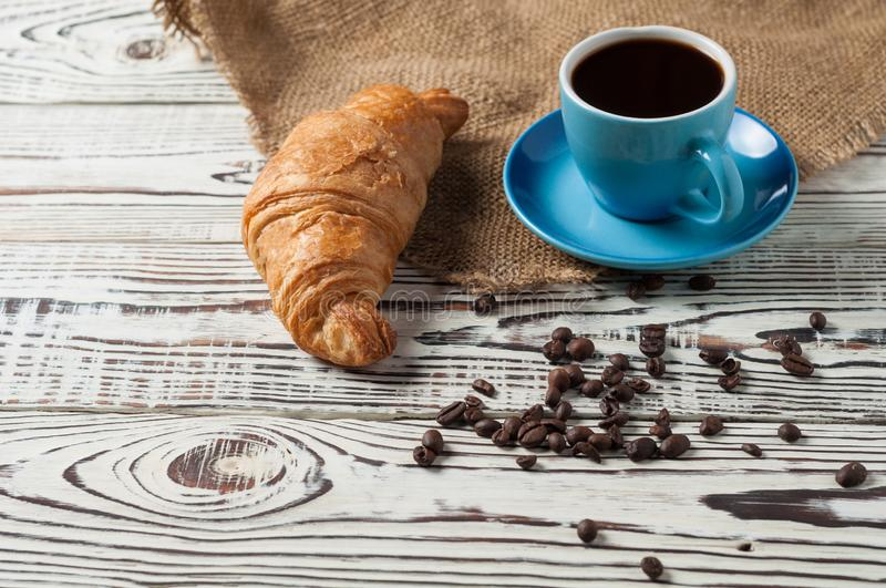 One whole baked croissant near full blue ceramic cup of fresh black coffee on sackcloth and old white wooden table. One whole baked croissant near full blue stock photo