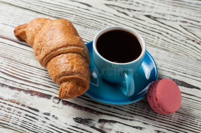 One whole baked croissant near pink macaroon and full blue ceramic cup of fresh black coffee on old rustic wooden table. One whole baked croissant near pink stock photos