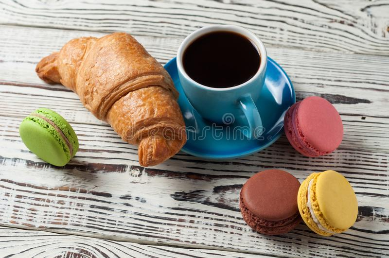 One whole baked croissant near various macaroons and full blue ceramic cup of fresh black coffee. On old white rustic wooden table royalty free stock photos