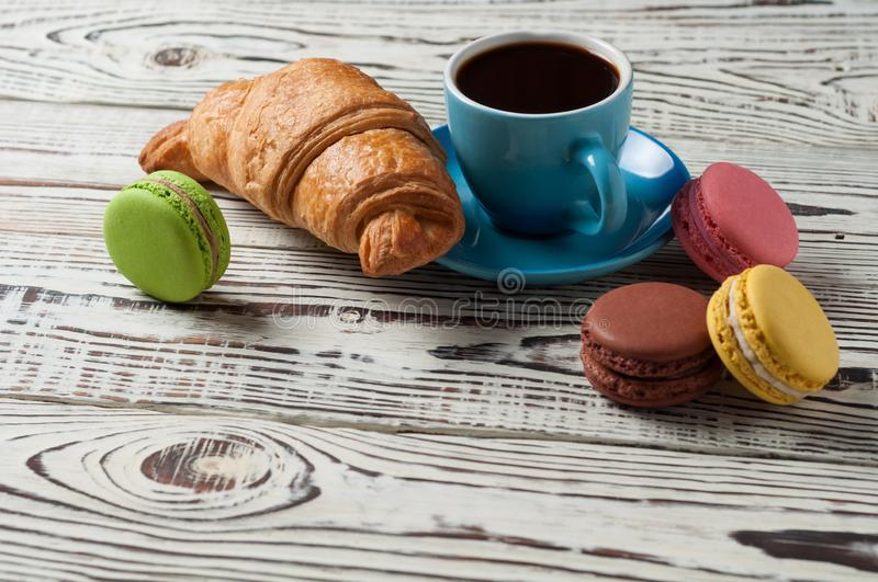 One whole baked croissant near various macaroons and full blue ceramic cup of fresh black coffee. On old white rustic wooden table royalty free stock photography