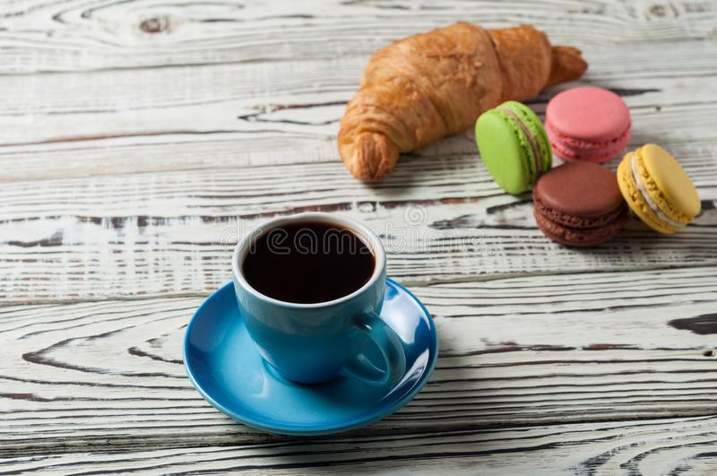 One whole baked croissant near various macaroons and full blue ceramic cup of fresh black coffee. On old white rustic wooden table stock photo