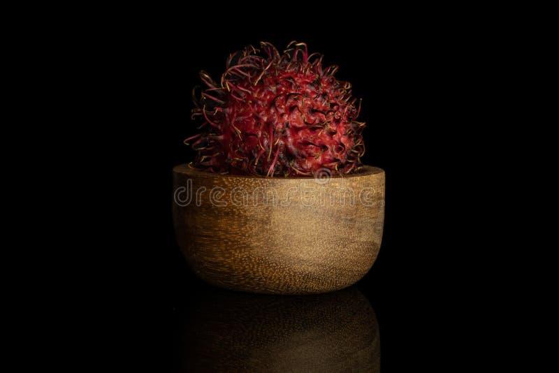 Fresh red rambutan isolated on black glass. One whole fresh red rambutan in wooden bowl isolated on black glass stock photos