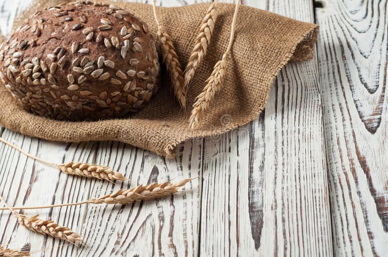 One whole loaf of rye bread with seeds of sunflower near sackcloth and spikelets of wheat lies on weathered white wooden table. One whole loaf of rye bread with royalty free stock photography