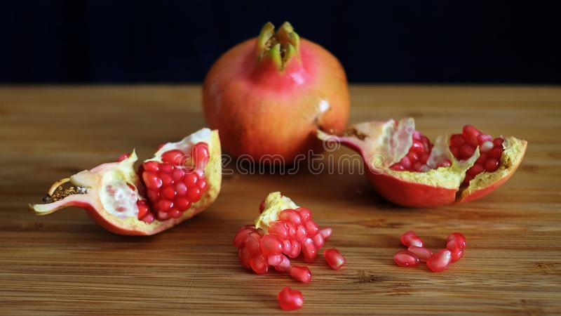 One whole and one open pomegranate or the fruit of Punica granatum resting on a wooden board with a dark background. One whole and one open pomegranate or the royalty free stock photo