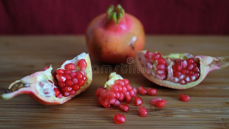 One whole and one open pomegranate or the fruit of Punica granatum revealing clusters of red seeds. One whole and one open pomegranate or the fruit of Punica stock photos