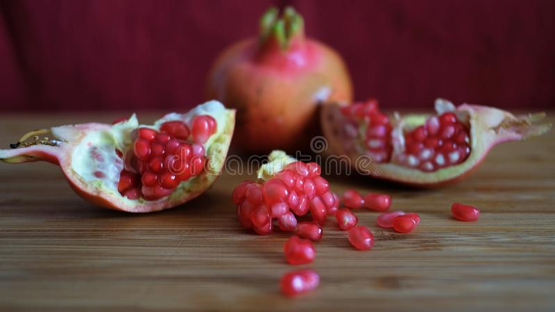 One whole and one open pomegranate or the fruit of Punica granatum. Revealing clusters of red, juicy seeds, white fibrous arils and thick, waxy peel resting on royalty free stock photo