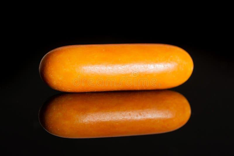 Licorice sweet comfit  on black glass. One whole orange sweet licorice comfit  on black glass stock image
