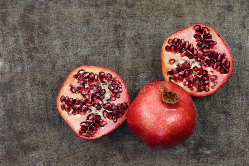 One whole pomegranate Punica granatum and two halves stock images