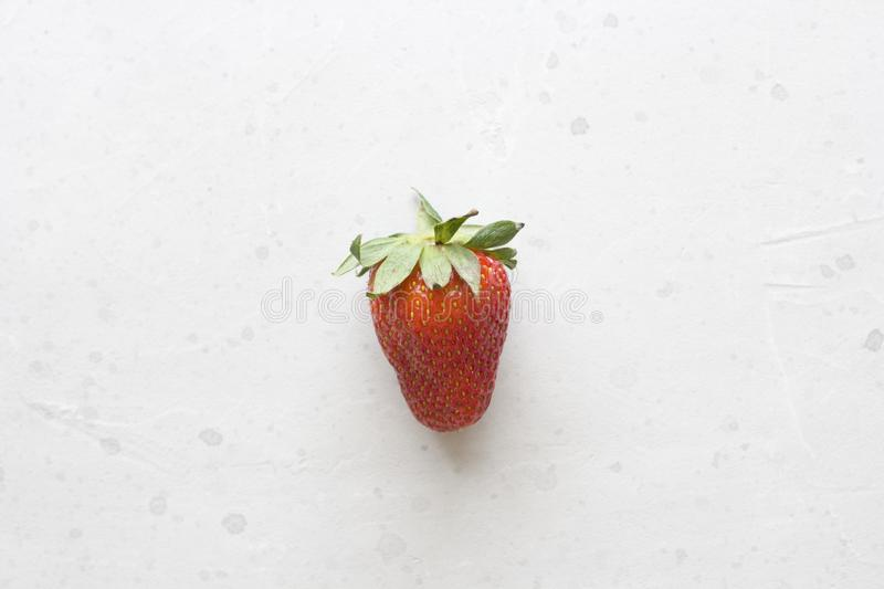 One whole red strawberry closeup lies on a light white concrete background. Minimalism. Top View, Copy Space For Your Text.  stock images