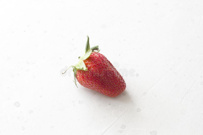 One whole red strawberry closeup lies on a light white concrete background. Minimalism. Top View, Copy Space For Your Text.  royalty free stock photography