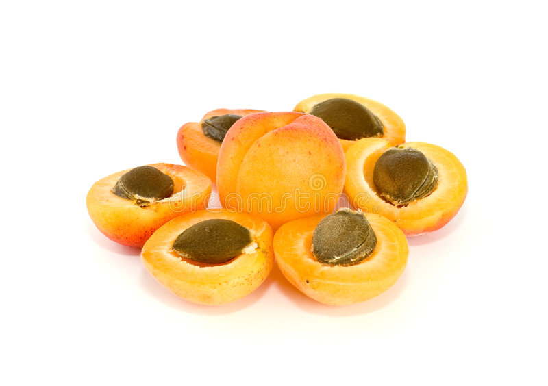 One whole and six apricot halves with kernels. Lying in form of flower isolated on the white background stock photo